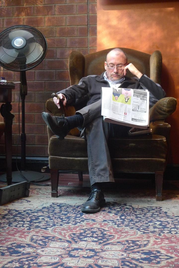Cigar Smoker reading the Sunday New York Times / Cigar Inn, New York, NY / Leica D-Lux 4